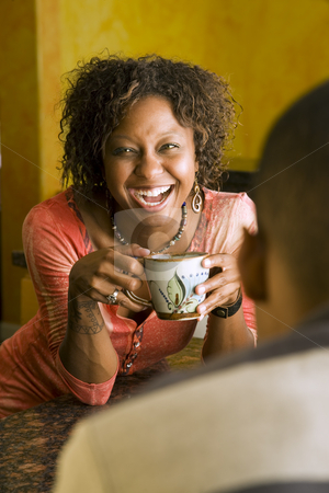 African-American woman talks to male in kitchen stock photo, Pretty African-American woman talks to male in kitchen by Scott Griessel