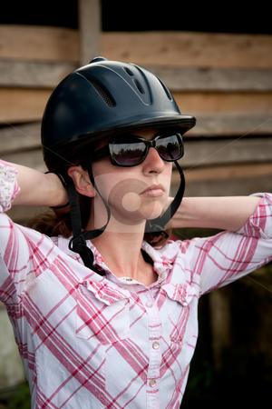 Costa Rican tourist putting on equestrian helmet stock photo, Female Costa Rican tourist putting on equestrian helmet by Scott Griessel