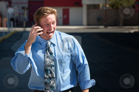 Good-looking guy excitedly talks on cell phone stock photo, Man yells into cell phone on downtown street by Scott Griessel