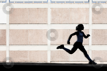 Physically fit woman runs for exercise stock photo, Woman in the shadows of building runs for exercise. by Scott Griessel