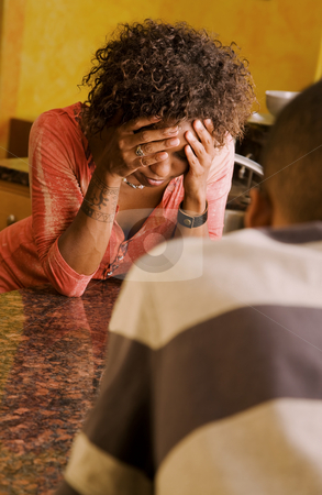 African-American woman and male talking in kitchen stock photo, Distraught African-American woman and male talking in kitchen by Scott Griessel