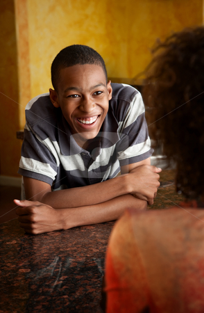 African-American young man and woman talking in kitchen stock photo, Handsome African-American young man and woman talking in kitchen by Scott Griessel