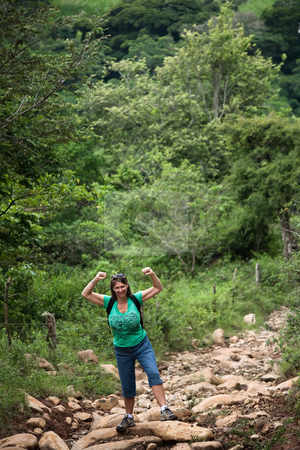 Female hiker flexing on a rugged rustic trail in Costa Rica stock photo, Female hiker flexing on a rugged trail in Costa Rica by Scott Griessel