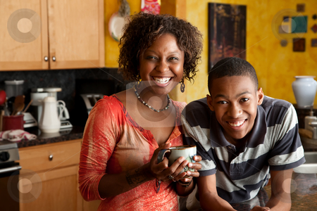 African-American woman and young man in kitchen stock photo, Attractive single-parent mom and son in kitchen by Scott Griessel