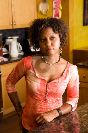 African-American woman in kitchen stock photo, Pretty woman standing at counter in kitchen by Scott Griessel