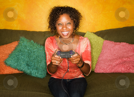 African-American woman plays video game stock photo, Attractive woman plays video game with hand held controller by Scott Griessel