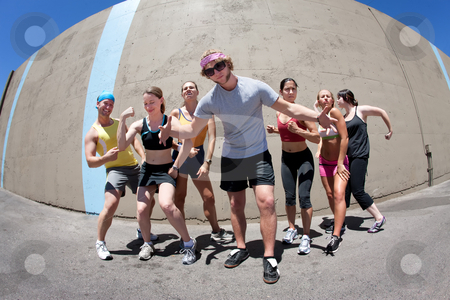 Man posing with fellow athletes stock photo, Handsome man posing with several fellow athletes by Scott Griessel