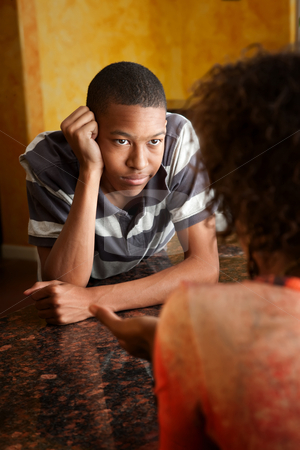 African-American teen talks with woman in kitchen stock photo, Handsome African-American teen talks with woman in kitchen by Scott Griessel