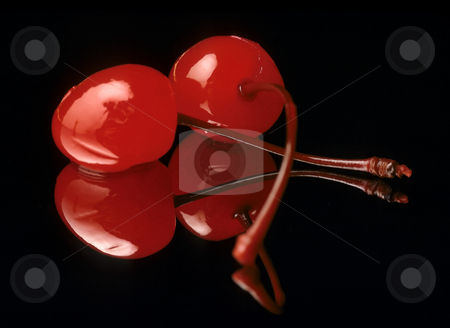 Cherries stock photo, Two maraschino cherries on a black reflective background by Christian Delbert