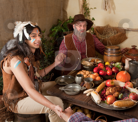 Thanksgiving reenactment stock photo, Reenactment scene of the first Thanksgiving Dinner in Plymouth in 1621 with a Pilgrim family and a Wampanoag Indian by Anneke
