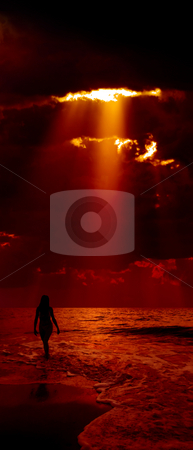 Girl on beach. stock photo, Silhouette of girl and dramatic dark red sky with sunbeam on background. by Oleksiy Fedorov
