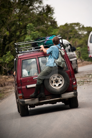 Man riding on the back of a van near Monteverde Costa Rica stock photo, Man riding on the back of a big van near Monteverde Costa Rica by Scott Griessel