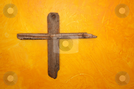 Wooden Cross stock photo, Rugged wooden cross hanging on yellow wall by Scott Griessel