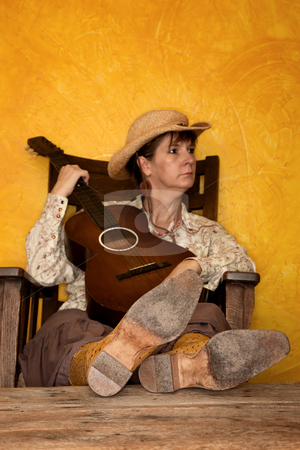Pretty Western Woman with Guitar stock photo, Pretty western woman in antique rocking chair with guitar by Scott Griessel