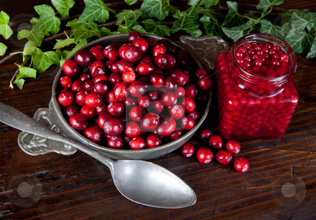 Bowl of cranberries stock photo, Thanksgiving still-life with cranberries and ivy leaves by Anneke