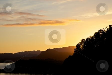 Yellow sunset stock photo, Yellow sunset to the west with the sun behind the trees. by Svein Hovland
