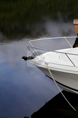 Moored yacht stock photo, Bow of a small yacht with reflections in the water. by Svein Hovland