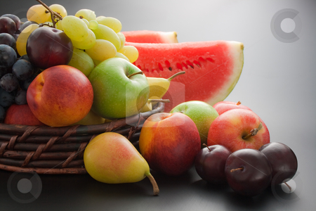 Fruits stock photo, Various fresh ripe fruits placed in a wicker basket and around on gray gradient background by Miroslav Ivanov