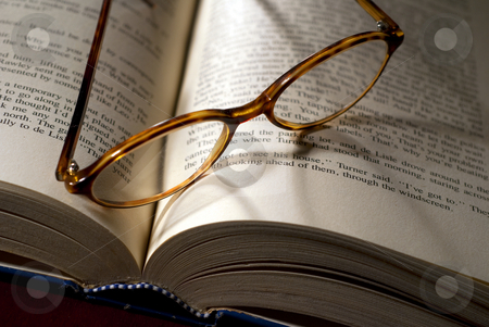 Reading glasses and book stock photo, Open book with reading glasses lying on top by Christian Delbert
