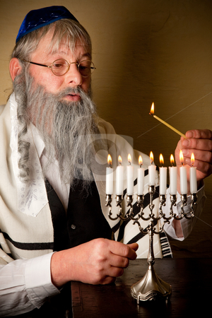 Lighting the menorah stock photo, Old jewish man with beard lighting the candles of a menorah by Anneke