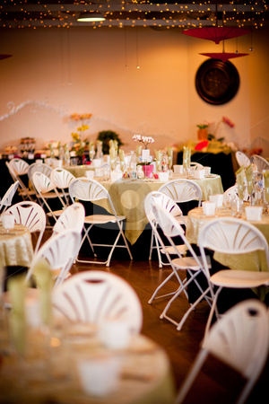 Indoor Wedding Reception Decoration stock photo, White folding chairs and yellow covered tables make up the decoration for this indoor wedding reception by Sharon Arnoldi