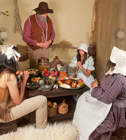 Thanksgiving table stock photo, Reenactment scene of the first Thanksgiving Dinner in Plymouth in 1621 with a Pilgrim family and a Wampanoag Indian by Anneke