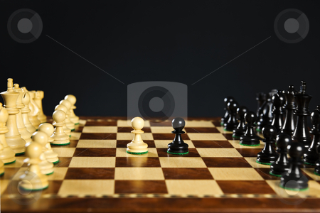 Chess pieces on board stock photo, Close up of chess pieces on wooden chessboard by Elena Elisseeva