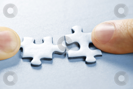 Puzzle pieces stock photo, Fingers pushing two matching puzzle pieces together by Elena Elisseeva