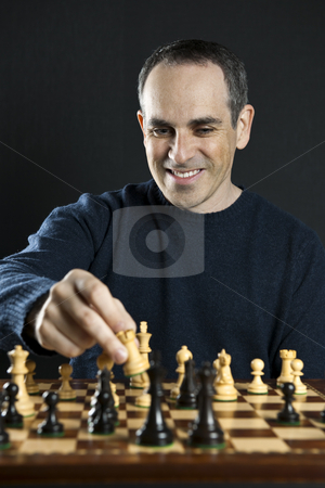 Man playing chess stock photo, Man moving a chess piece to win the game by Elena Elisseeva
