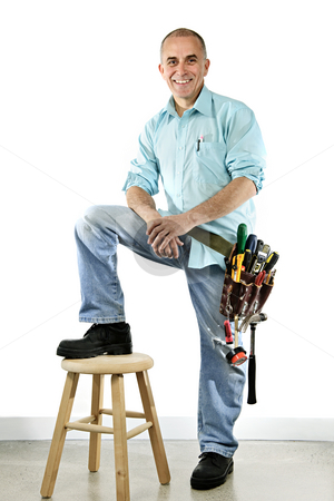 Smiling handyman stock photo, Portrait of smiling handyman with tool belt and stool by Elena Elisseeva