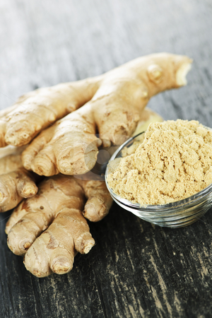 Ginger root stock photo, Fresh and ground ginger root spice on wooden table by Elena Elisseeva