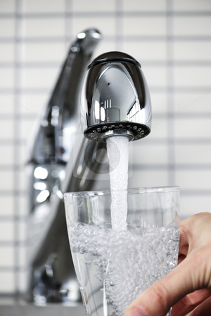 Filling glass of tap water stock photo, Filling glass of water from stainless steel kitchen faucet by Elena Elisseeva