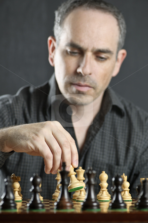Man playing chess stock photo, Man moving a chess pawn on wooden chessboard as first move by Elena Elisseeva