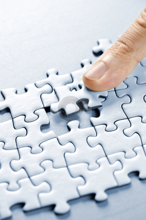 Puzzle pieces stock photo, Finger pushing missing puzzle piece into place by Elena Elisseeva