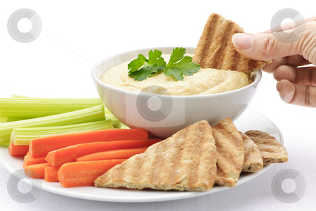 Hand dipping pita in hummus stock photo, Hand dipping slice of pita bread into bowl of hummus by Elena Elisseeva