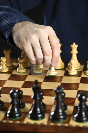 Hand moving pawn on chess board stock photo, Hand moving a pawn chess piece on wooden chessboard as first move by Elena Elisseeva