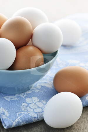 Eggs in bowl stock photo, Closeup of white and brown eggs in bowl by Elena Elisseeva