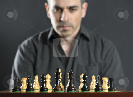 Man at chess board stock photo, Man looking at wooden chess board thinking about first move by Elena Elisseeva
