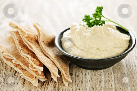 Hummus with pita bread stock photo, Bowl of fresh hummus dip with pita bread slices by Elena Elisseeva