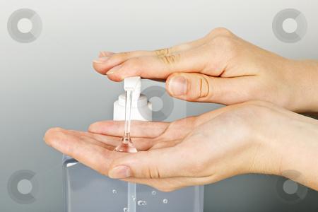 Hands applying sanitizer gel stock photo, Female hands using hand sanitizer gel pump dispenser by Elena Elisseeva