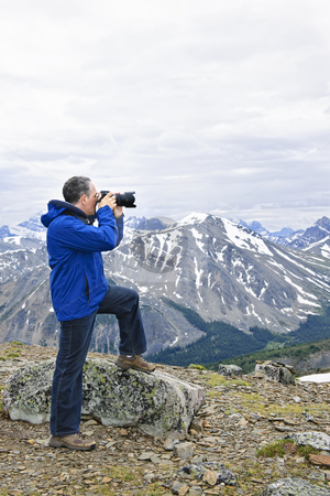 Photographer in mountains stock photo, Male photographer taking pictures in Canadian Rocky Mountains in Jasper National Park by Elena Elisseeva