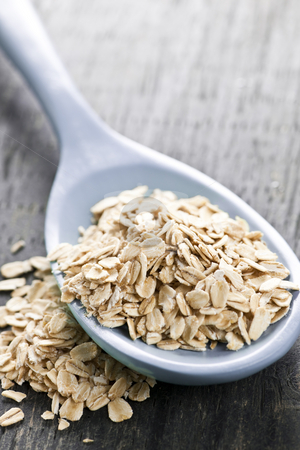 Spoon of uncooked rolled oats stock photo, Nutritious rolled oats heaped on a spoon by Elena Elisseeva