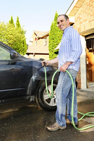 Man washing car on driveway stock photo, Man washing his car on the driveway by Elena Elisseeva