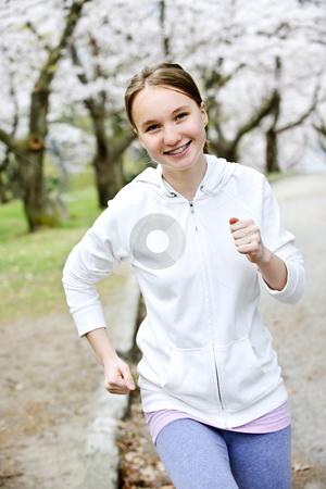 Girl jogging in park stock photo, Beautiful teenage girl jogging in park with blooming apple trees by Elena Elisseeva