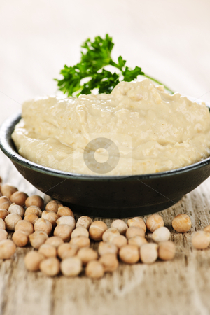 Hummus with chickpeas stock photo, Bowl of fresh hummus with raw organic chickpeas by Elena Elisseeva
