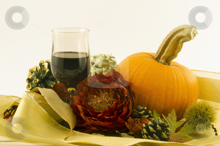 Celebrate Autumn stock photo, Red wine in an autumn tone glass in a celebratory still life with an orange pumpkin, red blossom, seasonal chestnut burr, pine cone and dry leaves offer an elegant toast to the celebration of autumn by Florence McGinn