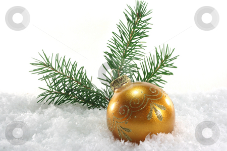 Christmas ball stock photo, One golden Christmas ball with pine branches lies in the snow by Marén Wischnewski