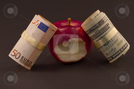 Two Economies Struggle stock photo, Two currencies, euro and dollar, lean against a red apple with a bite taken out of it, representative of economic struggles as well as personal financial issues within those connected economies by Florence McGinn