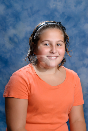 Preteen Portrait stock photo, A smiling preteen girl portrait with a blue background by Richard Nelson