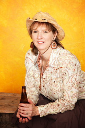 Pretty Western Woman with Beer stock photo, Pretty western woman in cowboy shirt and hat with beer bottle by Scott Griessel